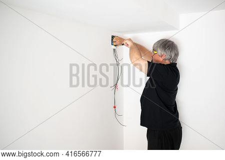 Electrician Working In Home Renovation. New Electrical Installation For Energy Improvement.