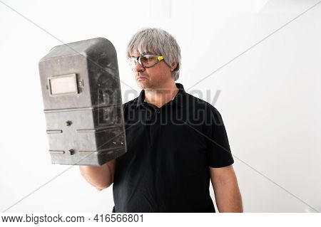 Repairman Holds A Welding Protection Mask For Home Repairs, Insulated On White Background.