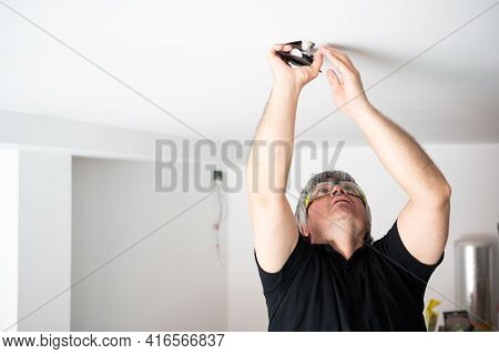 Professional Electrician In Home Reforms, Installing New Led Bulbs To Reduce Electricity Consumption