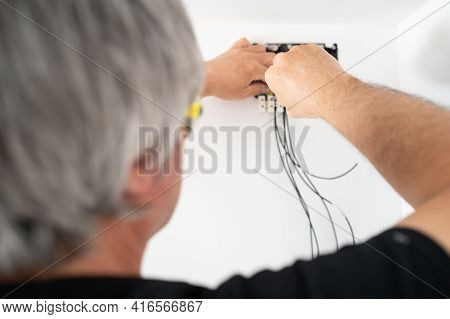 Close Up Of Professional Repairman Fixing Wires In Electrical Installation