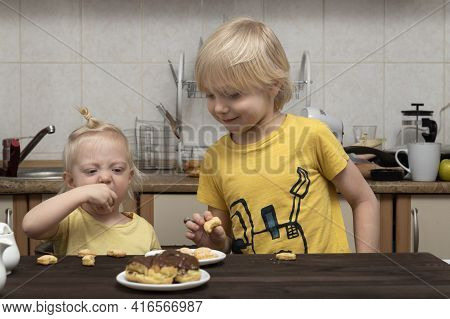 Fair-haired Brother And Sister Are Having Breakfast In Kitchen. Friendly Family.