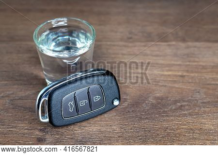 Close-up Of New Car Keys Near A Shot Glass Of Alcohol On A Dark Wooden Background