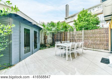 Modern Table With Chairs Located On Tiled Floor Near Thatch Fence In Backyard Of Blue House