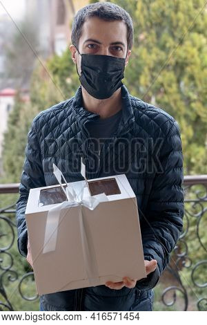 Serious Middle-aged Man Stands In Front Of The Door Holding Cardboard Box With Bow, Gift For Friend.