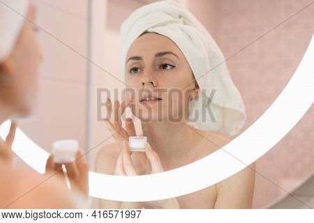 Woman Standing Near Mirror In The Bathroom And Applying Moisturizer On Her Face