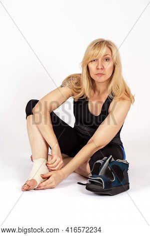 Middle Aged Caucasian Woman With Bandage On One Leg Of Elastic Tape, Sitting On The Floor. Special O