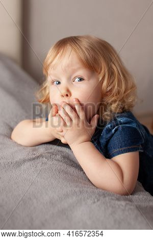Portrait Baby Toddler Toddler Blonde With Blue Eyes Leaned Her Hands Bed And Covered Her Mouth With