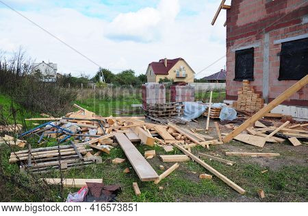 A Mess On The Construction Site. Scattered Wood Boards, Rafters, Bricks And Other Building Materials