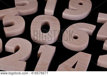 Large Random Wooden Numbers Laying Down On A Black Background Table. Hardwood Characters With Copy S