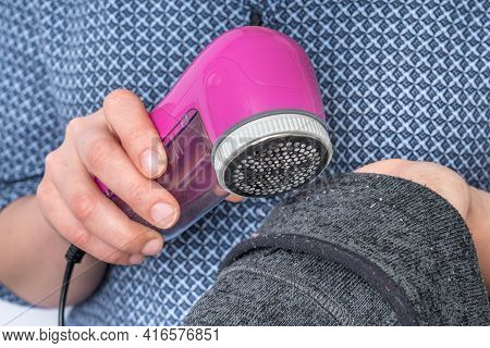 Woman Is Removing Lint With Fabric Shaver Or Fuzz Remover - Clothes Care Concept