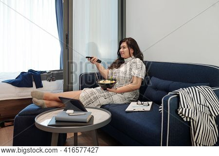 Pretty Elegant Plus Size Woman Sitting On Sofa, Eating Fruit Salad And Watching Tv Show