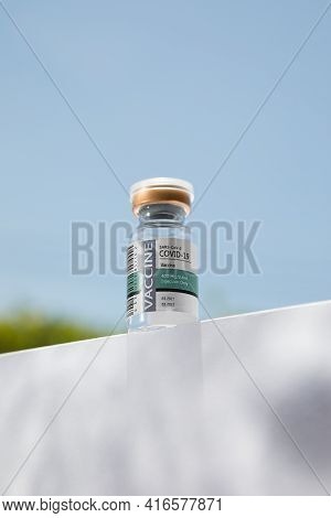 No Logos Or Trademarks!  Self Made Labels! Close Up View Of Ampule With Covid Vaccine On Blue Back