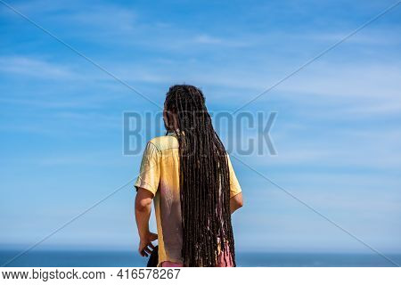 Rear View Of Man With Dreadlocks Looking At The Sky