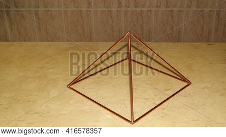 Copper Pyramid. Pyramid Based On Travertine Marble With A Top-down View, With Shadow, Represents One