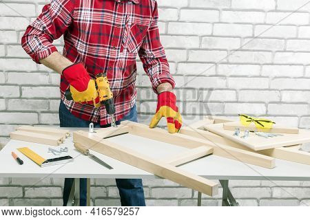 Assembling Furniture From Wooden, Using A Cordless Screwdriver. The Handyman In Assembling The Chair