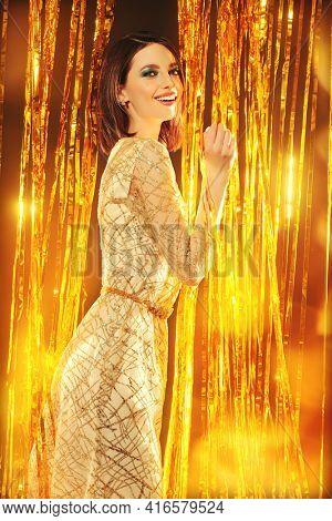 Holiday fashion. Portrait of a high fashion model girl posing in an expensive evening dress against a background of shiny gold curtains.