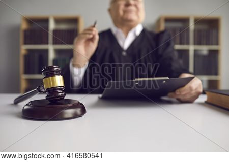 Senior Judge With Pen And Clipboard Sit At Table Shot With Focus On Mallet