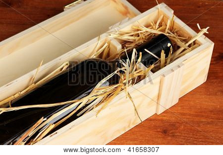 Wooden case with wine bottle on table