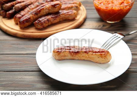 Grilled Sausage On Plate On Brown Background. Top View. Vertical Foto