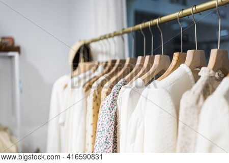 Row Of Different Female Clothes Hanging On Rack In Hipster Fashion Show Room In Shopping Mall. Trend