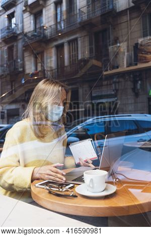 Young Blond Woman With A Face Medical Mask Working With Laptop In Cafe. Writing. Online Courses, Stu