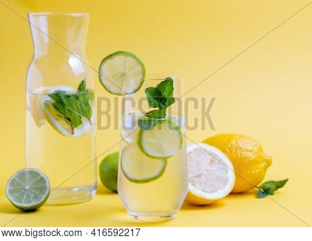 Glass Of Fresh Water With Lime Slices And Mint Leave On Yellow Background Prepared For Detoxificatio