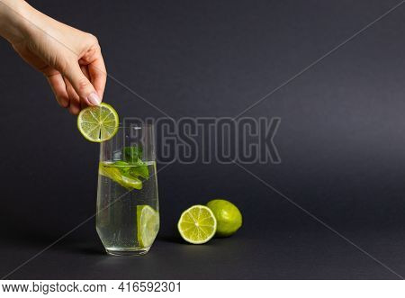 Glass Of Detox Water With Fresh Lime Slices And Mint Leave On Black Background. Woman Hand Preparing