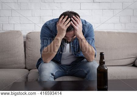 Weakness, Depression, Addiction And Alcoholism. Millennial Upset Man Sitting On Sofa