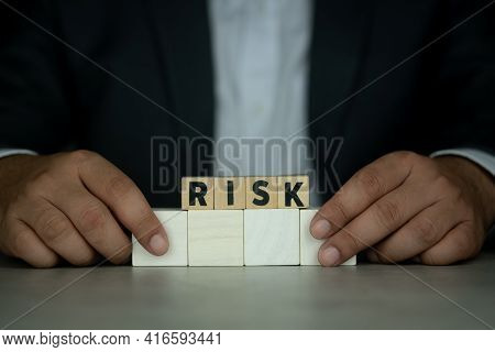 Businessman In Suit Hold Wooden Cubes With Risk Word. Risk Management Concept. Risk Assessment, Deci