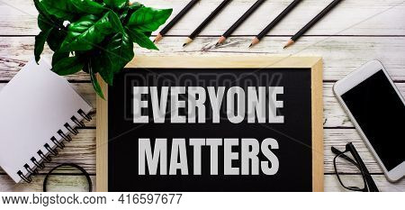 Everyone Matters Is Written In White On A Black Board Next To A Phone, Notepad, Glasses, Pencils And