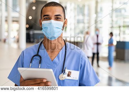Portrait of multiethnic doctor using digital tablet wearing safety surgical face mask at private clinic during covid pandemic. Successful smiling indian nurse wearing mask for safety against covid-19