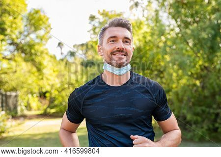 Happy mature man running in park with face mask during covid-19 pandemic. Smiling mid adult man jogging outdoor with surgical face mask for safety against covid19 outbreak. Fitness mid athlete jogging