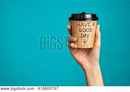 Close up of hand of young woman holding take away coffee cup. Woman hand holding a coffee paper cup isolated on blue background. Morning disposable mug with message of good day written over it.
