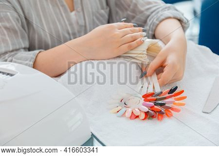 Female Hands With Artificial Acrylic Nails Picks Up New Nail Polish Color During Manicure Procedure.