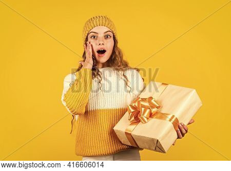 Kid Little Girl Hold Gift Box With Ribbon On Yellow Background. Christmas Present For Daughter. Enjo