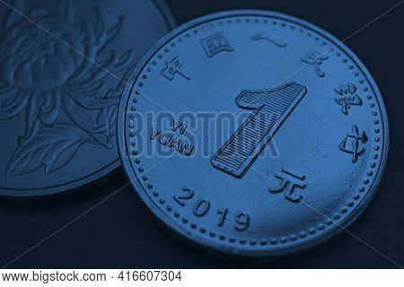 Translation: People's Bank Of China, One Yuan. Chinese Coins Close-up. Dark Blue Tinted Background O