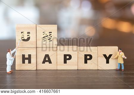 Worker Team On Unhappy Word In Wooden Alphabet Letters With Prefix Un Crossed Out, Leaving The Word