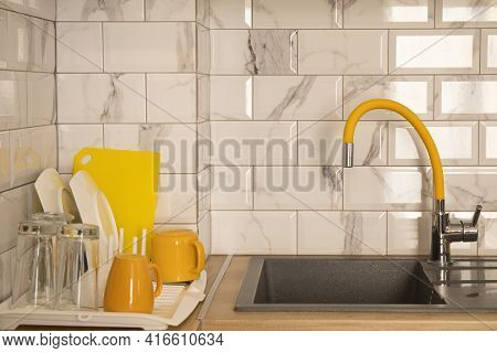 Stack Of Dishes On The Dryer Near Grey Granite Sink With Yellow Basin