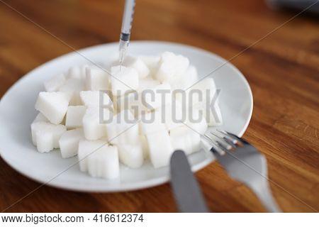 Insulin Syringe Inserting Into Lump Of Sugar On Plate Closeup
