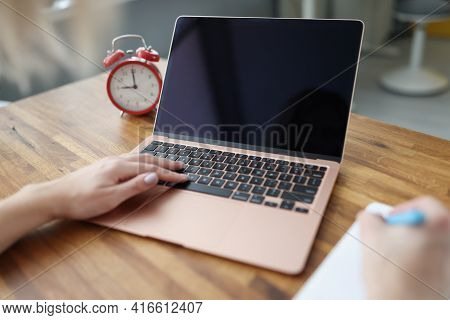 Woman Typing On Laptop Keyboard And Writing In Notepad Closeup