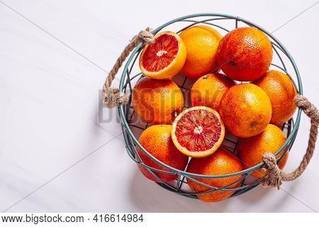 Sicilian Blood Oranges In A Metal Basket On A Natural Marble Background. Top View, Copy Space.