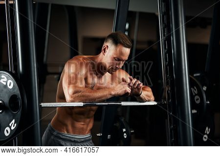 Closeup Portrait Of A Muscular Man Workout With Barbell At Gym. Brutal Bodybuilder Athletic Man With