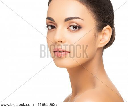 Face of a beautiful oriental brunette girl. Close-up portrait of young and attractive woman with brown eyes.