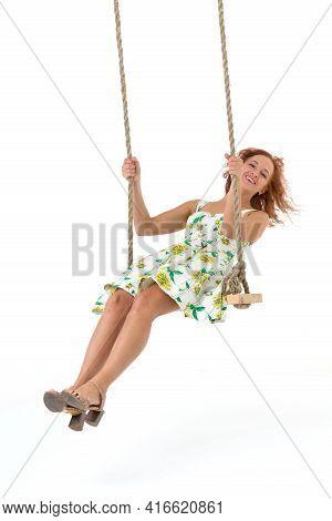 Beautiful Young Woman Swinging On Rope Swing