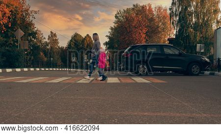 Mother And Daughter Cross The Road At A Pedestrian Crossing. White-yellow Zebra. Pedestrian Crossing