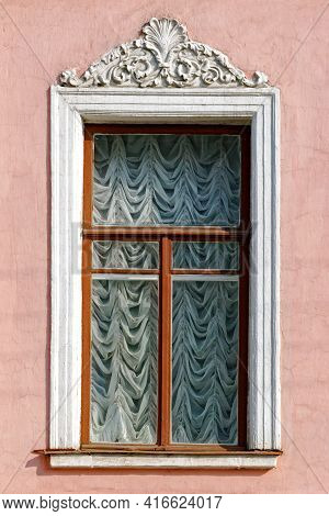 Rectangular Window With A Bas-relief On The Background Of A Pink Stucco Wall. From The Windows Of St