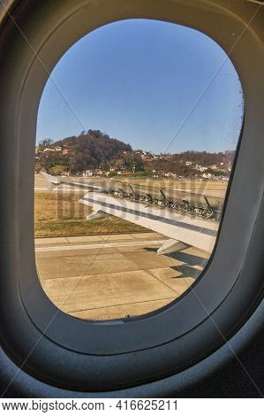 View From The Porthole Glass. The Wing Of An Airplane Landing On The Tarmac. Sochi, Russia