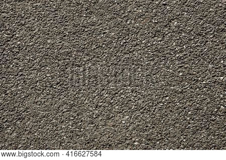 The Texture Of The Rough Gray Background Of The Wall Interspersed With Small Pebbles Is Evenly Illum