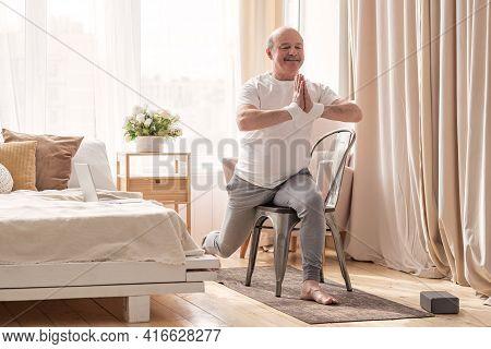 Elderly Man Practicing Yoga Asana Warrior Using Chair