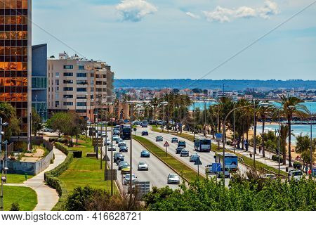 PALMA, SPAIN - MAY 09, 2019: Vehicles drive on urban road along seaside promenade and modern buildings in Palma - capital and largest city of  Balearic Islands, famous resort and tourist destination.